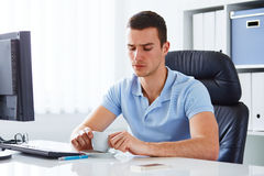 Man in office holding coffee. Young man in office holding coffee cup Stock Image