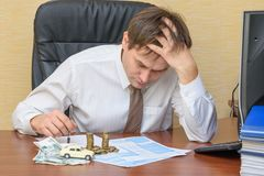 The man at the office, holding his head looking at the notice of the accident with the money and the machine lying on the document. S on the table stock photography