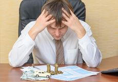 The man at the office, holding his head looking at the notice of the accident with the money and the machine lying on the document. S on the table stock photo