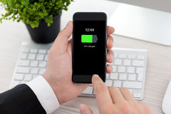 Man in office holding phone with charged battery on screen Stock Photos
