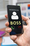 Man in office holds smartphone with incoming call from boss Stock Photography