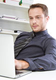 Man in office with laptop Stock Photography