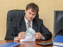 The man in the office looking at the money in an envelope. On tha table Royalty Free Stock Photography