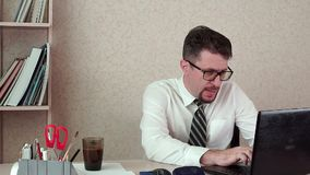 Man office manager with a beard and glasses, drinking coffee for a laptop. The morning of a working day in the office stock footage