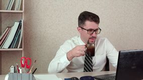 Man office manager with a beard and glasses, drinking coffee for a laptop. The morning of a working day in the office stock video