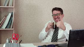 Man office manager with beard and glasses, drinking coffee, shows thumb up. On camera. The morning of a working day in the office stock footage