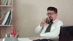 Man office manager with a beard and glasses, happy drinking coffee. The morning of a working day in the office stock video footage