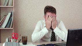 Man office manager has a headache. He`s sitting at his laptop with coffee. stock video footage