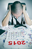 Man in the office after a new years party. A young man in the office with his head in his hands after a new years party, with a calendar of 2015 and confetti on Royalty Free Stock Photo