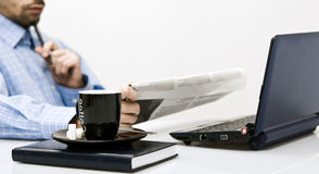 Man at office, reading newspaper. Man at office reading newspaper, with coffee in front Stock Photography