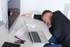 Man at the office relaxing. Man in a suit sleeps at his desk in his office Royalty Free Stock Photography