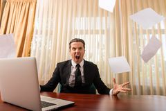 Man in office scream and paper fly Stock Photos