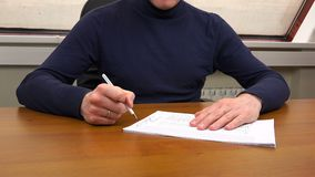 A man at the office signs a contract.  stock video footage