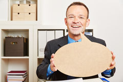 Man in office with speech bubble Stock Photography