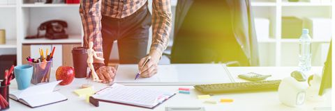 A man in the office is standing near the table and draws a marker on the magnetic board. A bearded man in a plaid shirt, glasses and dark trousers works in a royalty free stock photo