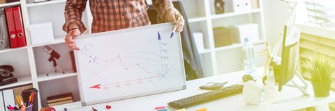 The man in the office is standing near the table and explains the schedule drawn on the magnetic board. A bearded man in a plaid shirt, glasses and dark stock image