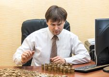 The man in the office at the table believes coins and adds them columns.  Royalty Free Stock Photos