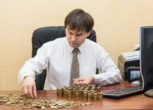 The man in the office at the table believes coins and adds them columns.  Royalty Free Stock Photography