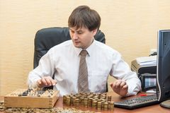 The man in the office at the table believes coins and adds them columns.  Stock Images