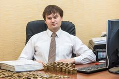 The man in the office at the table believes coins and adds them columns.  Stock Photo