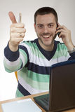 Man at the office table showing thumb up, smiling Royalty Free Stock Image