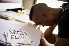 Man at office and text summers end. Closeup of a concerned man sitting at his office desk and a note in the foreground with the text summers end handwritten in Stock Image