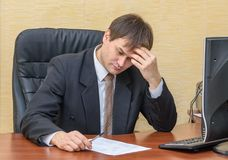 The man in the office thoughtfully looking into the document. On the table Stock Image