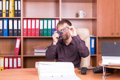 Man in office wipes glasses Royalty Free Stock Photography