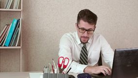 A man is an office worker with a beard and glasses slyly looking at a laptop. stock footage