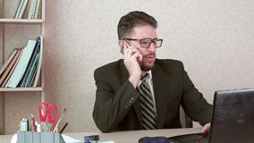 Man office worker with a beard and glasses talking to a client on a smartphone. stock footage