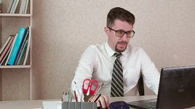 A man is an office worker with a beard and glasses working at a laptop stock video