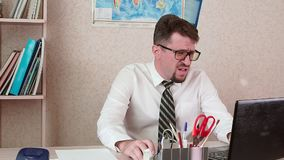 A man is an office worker with a beard and glasses working at a laptop stock footage