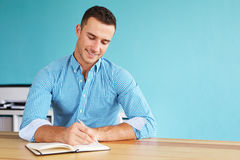 Man in the office writing plan in diary Stock Photos