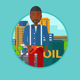 Man with oil barrel and gas pump nozzle. African-american man standing near oil barrel. Man holding gas pump nozzle on a city background. Man with gas pump and Stock Photography