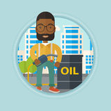Man with oil barrel and gas pump nozzle. An african-american man standing near oil barrel. Oil worker holding gas pump nozzle on a city background. Oil industry Royalty Free Stock Photos