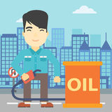 Man with oil barrel and gas pump nozzle. An asian man standing near oil barrel. Man holding gas pump nozzle on a city background. Man with gas pump and oil Royalty Free Stock Images