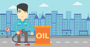 Man with oil barrel and gas pump nozzle. An asian man standing near oil barrel. Man holding gas pump nozzle on a city background. Man with gas pump and oil Stock Images