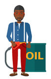 Man with oil can and filling nozzle. An  african-american man standing beside the oil can and holding filling nozzle vector flat design illustration  on white Royalty Free Stock Image