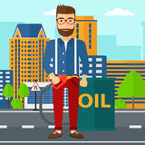 Man with oil can and filling nozzle. A hipster man with the beard standing beside the oil can and holding filling nozzle on a city background vector flat design Stock Photo