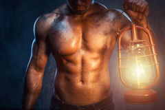 Man with oil lamp. Muscular man holding oil lamp Royalty Free Stock Image