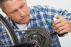 Man Oiling Bicycle Chain Royalty Free Stock Images
