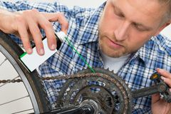 Man Oiling Bicycle Chain Stock Image