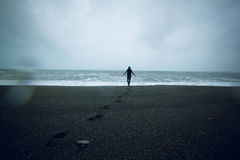 Man going on black sand on the background of sea, Iceland. Man goind on black sand beach in Iceland. Man looking at ocean sea in a rainy day. Footprints in the Stock Photography