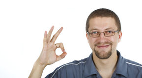 Man with ok sign. A young smiling man with glasses wearing blue shirt is showing the ok sign with his right hand, looking into the camera Stock Photography
