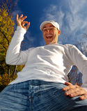 Man with ok sign in autumn. Bottom-up view to a man with ok sign (sky background Royalty Free Stock Images