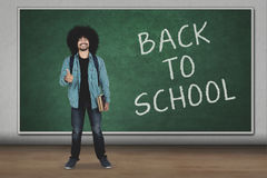 Man with ok sign and back to school word. Young man standing in the classroom while showing ok sign with back to school word on chalkboard Royalty Free Stock Photography