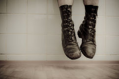 Man in old boots hanging in the air. Old military boots captured during jump Royalty Free Stock Image
