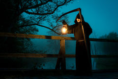 Man on old bridge with scythe and oil lamp. In Halloween holiday Stock Photo