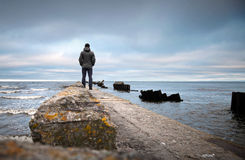 A man on the old broken pier Stock Photo