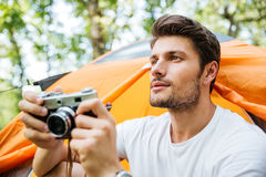Man with old camera sitting near touristic tent in forest Royalty Free Stock Images